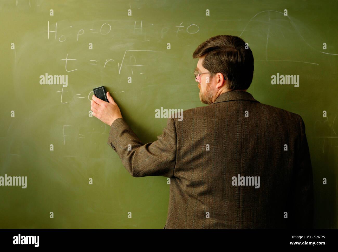 Lehrer, die mathematische Formel aus grünen Tafel löschen Stockbild