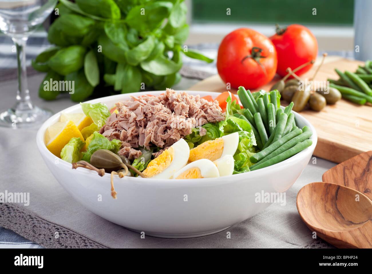 Salat Nicoise mit Zutaten im Hintergrund. Stockbild