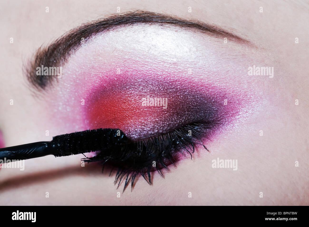 Frau, die Anwendung von Mascara farbigen Lidschatten Make-up Stockbild