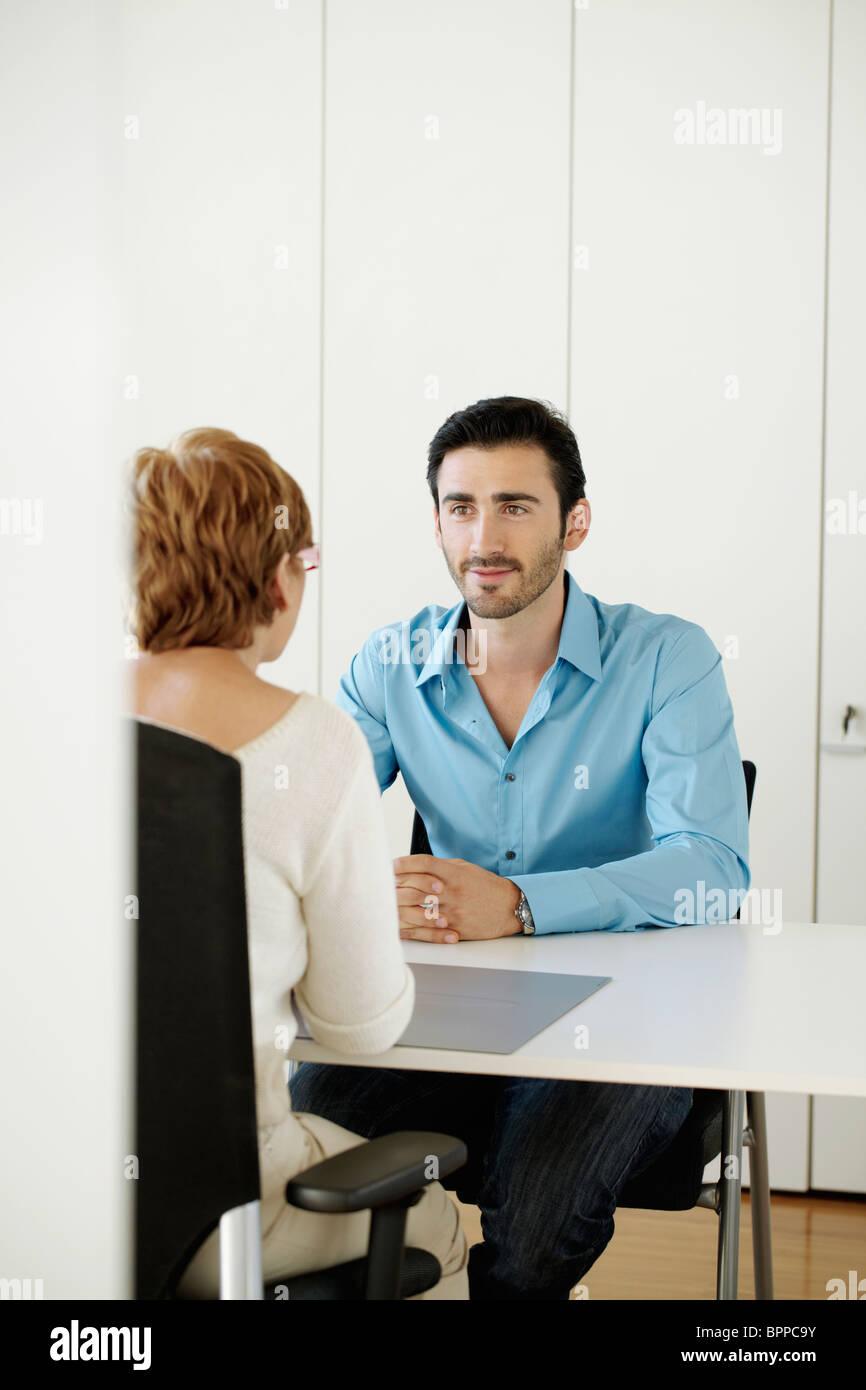 Mann gegenüber der Frau im Büro sitzen Stockbild