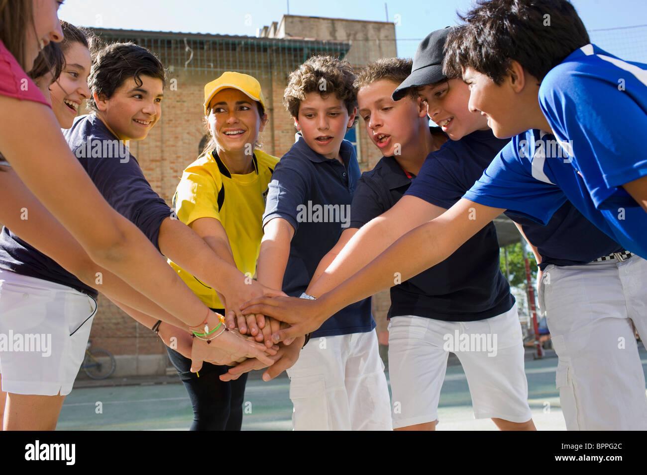Trainer und Kinder stehen in einem Kreis Stockfoto