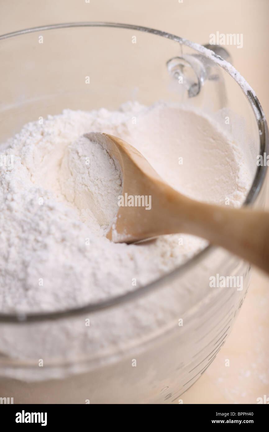Schüssel mit Mehl und Löffel Stockbild