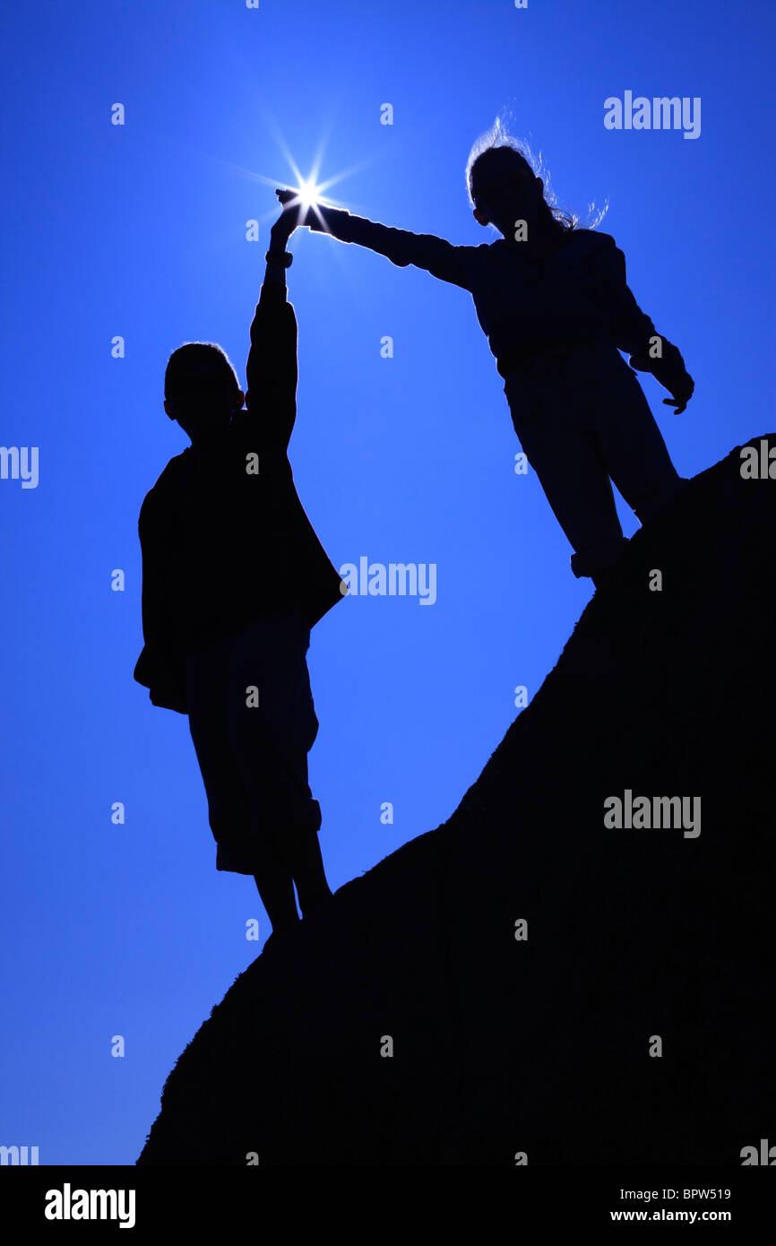 Silhouette der beiden Kinder Hand in Hand mit einem Sunstar Blendenfleck auf Herm Island genommen Stockbild