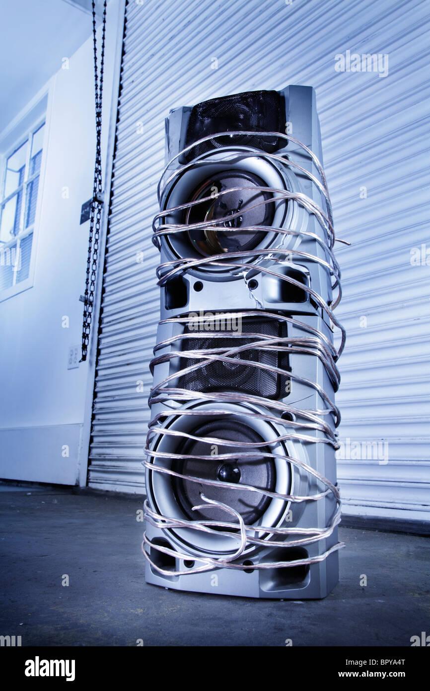 Defekte Lautsprecher umhüllt von Drähten in einer industriellen Umgebung Stockbild