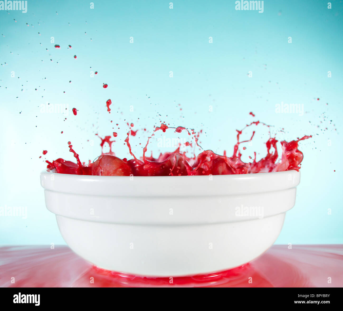 Rote Flüssigkeit sprudelt und spritzt in einer weißen Schüssel Stockbild