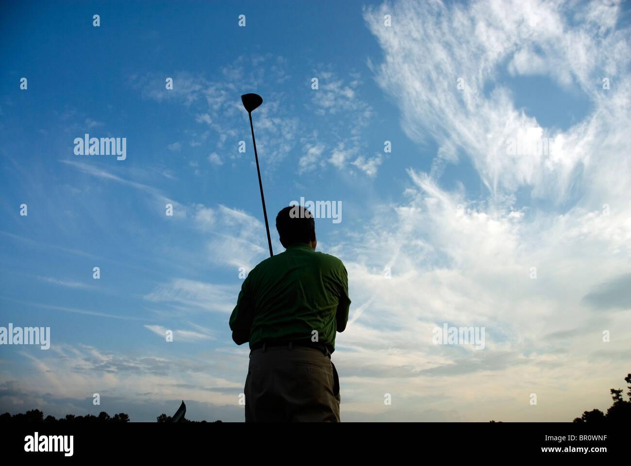Ein Mann ist Sillhouetted gegen den Himmel halten einen Golfclub, Georgia. Stockbild