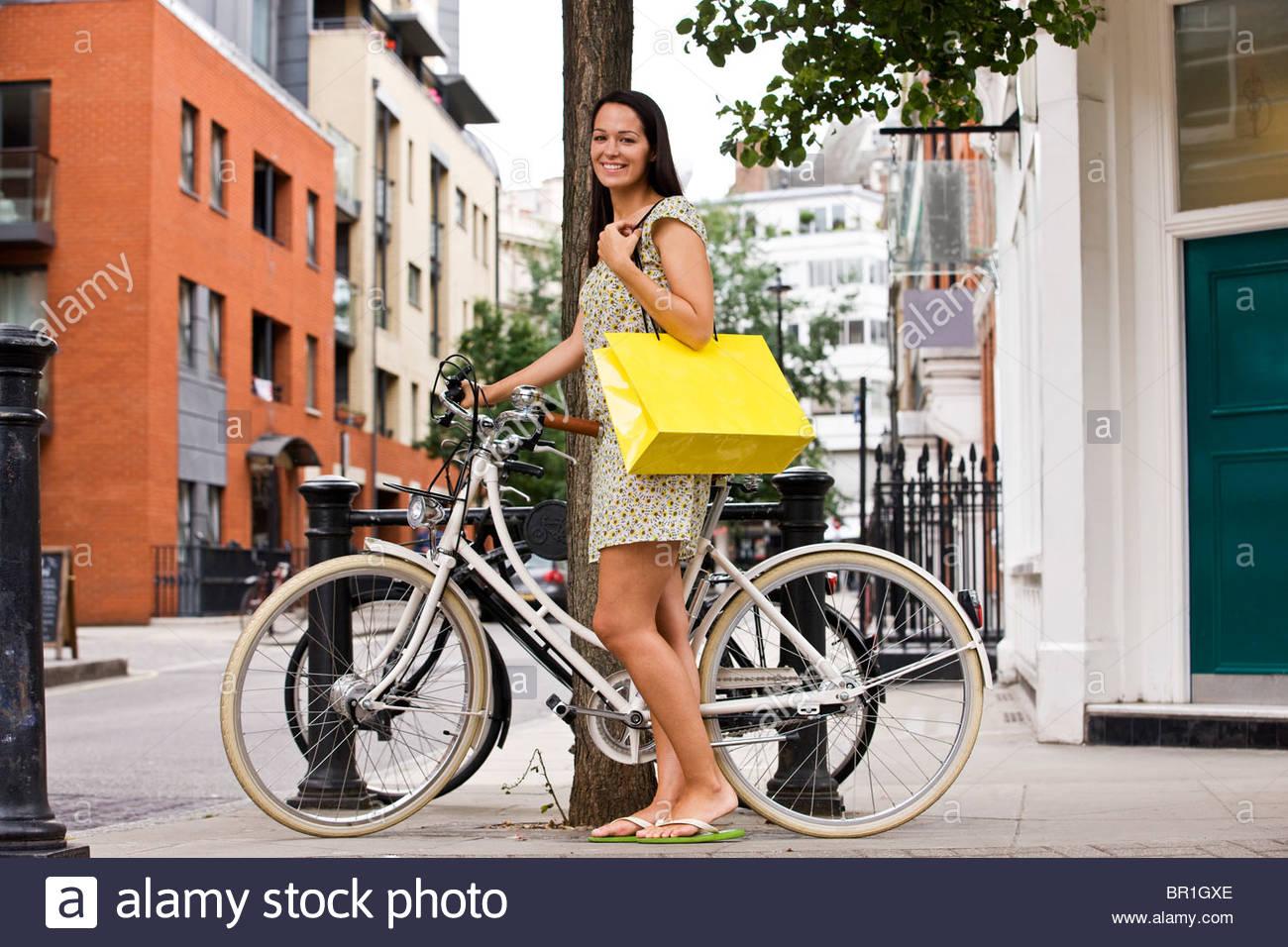 Eine junge Frau neben ihr Fahrrad steht, eine Einkaufstasche tragen Stockbild