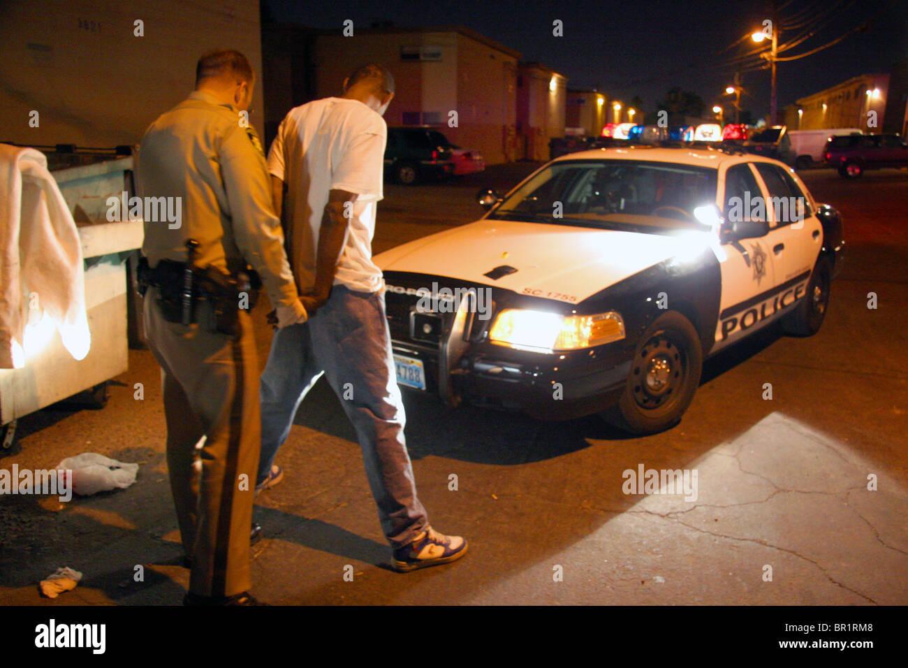 Polizist in Las Vegas Handschellen einen schwarzen Mann in einer Gasse in der Nacht. Stockbild