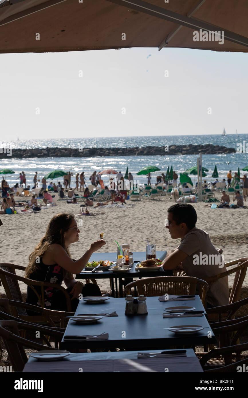 Ein paar Speisen Sie in einem Strandrestaurant, Tel Aviv, Israel Stockbild