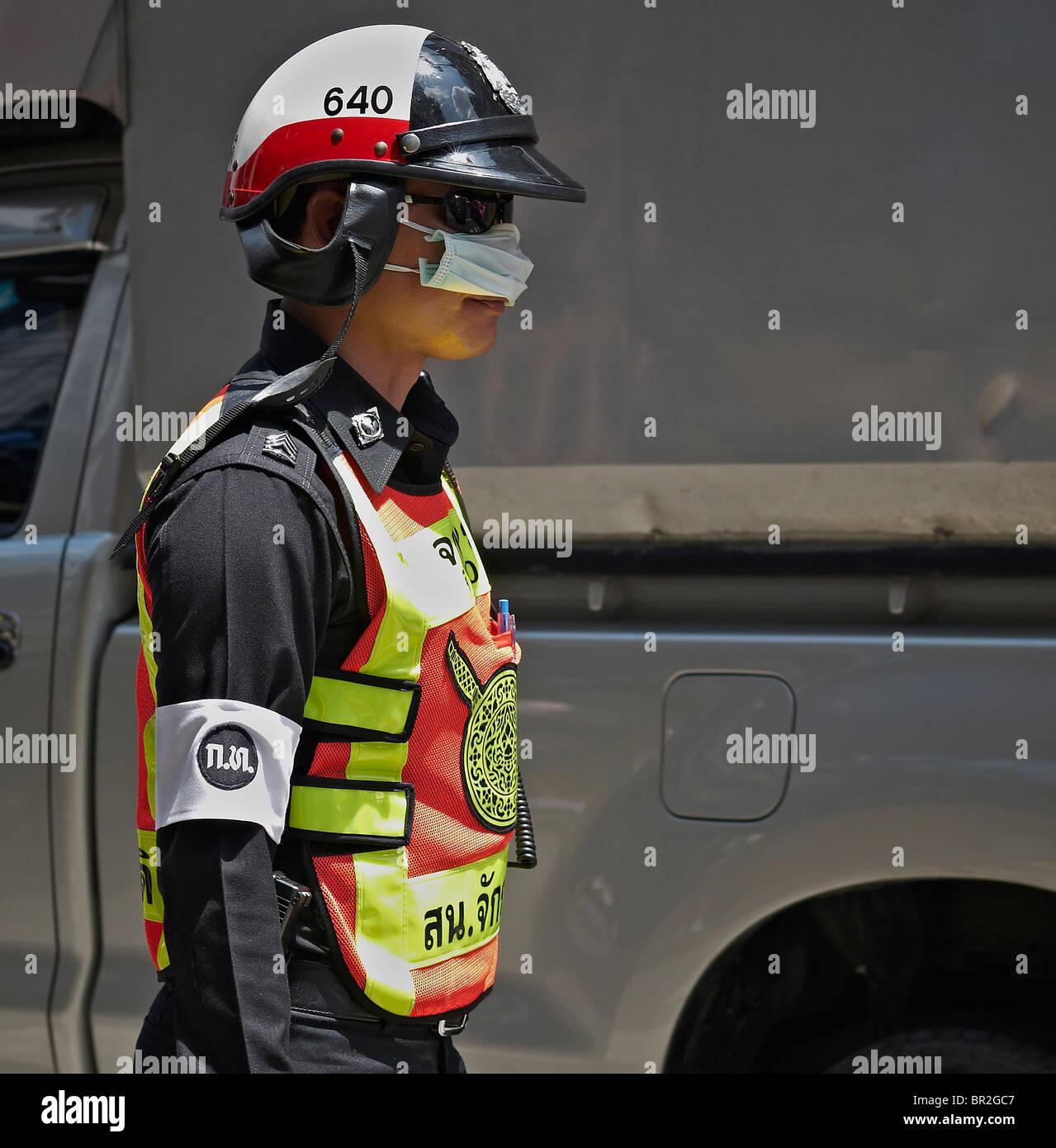 Thailändische Polizisten tragen eine Anti-Verschmutzung Maske in Bangkoks hohe Verschmutzung des Verkehrsflusses. Stockbild