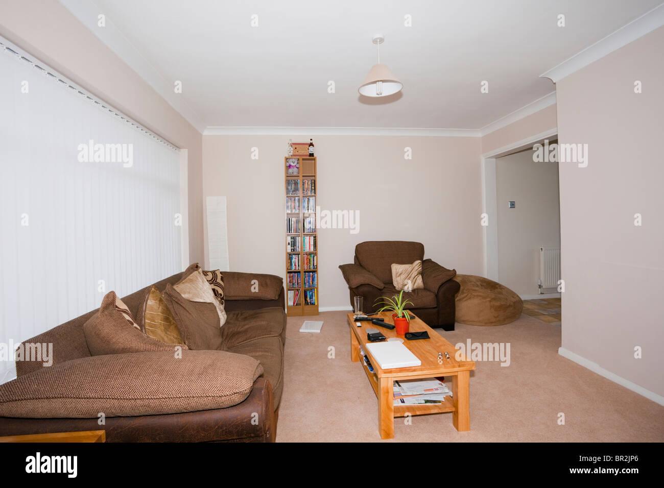 Sofa, Sessel und Tisch in einem ordentlich modernen minimalistischen Wohnzimmer mit Fenster-Vorhänge im englischen Stockbild
