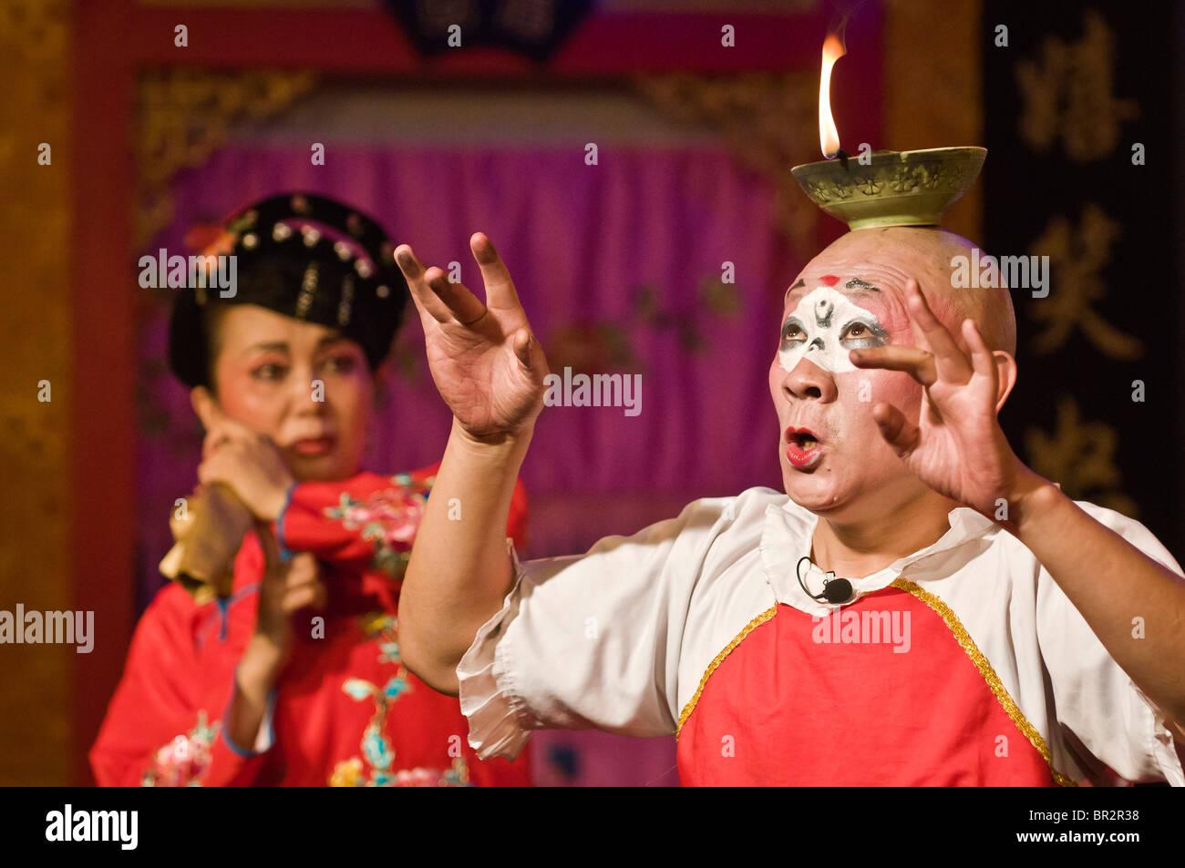 Schauspieler gleicht Öllampe in Sichuan Oper am Shufenyayuan Teehaus, Chengdu, Provinz Sichuan, China Stockbild