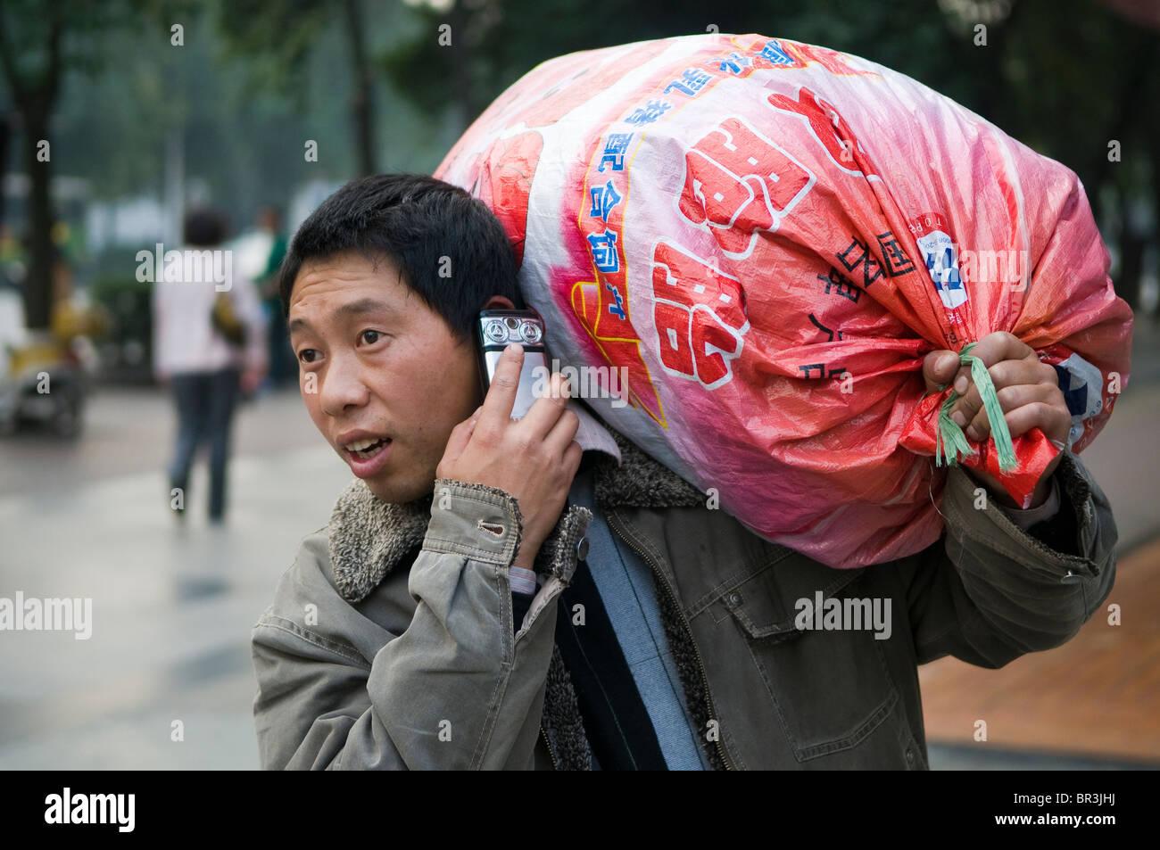Arbeiter trägt schweren Sack während des Gesprächs auf Mobiltelefon, Chengdu, Sichuan Provine, China Stockbild