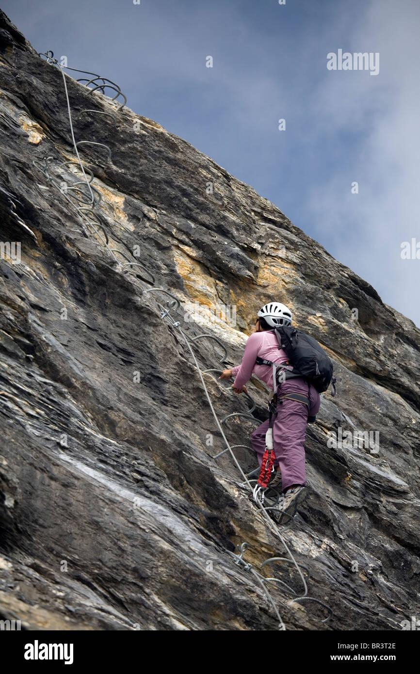 Eine junge Frau, die einen Aufstieg eingebettet in den Felsen während Beteiligung an den Sport Via Ferrata Stockbild