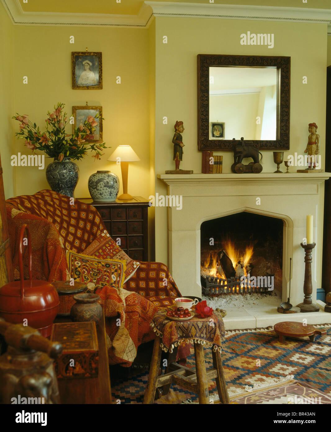 Sessel rot gemustert  Gemusterte rote werfen und Kissen Sessel neben brennenden Feuer im ...