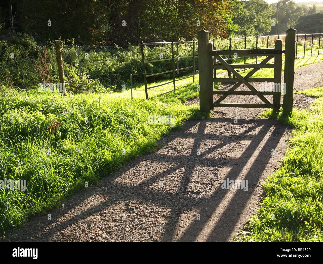 Hölzernes Tor wirft einen langen Schatten auf einem Pfad in der späten Nachmittagssonne Stockbild