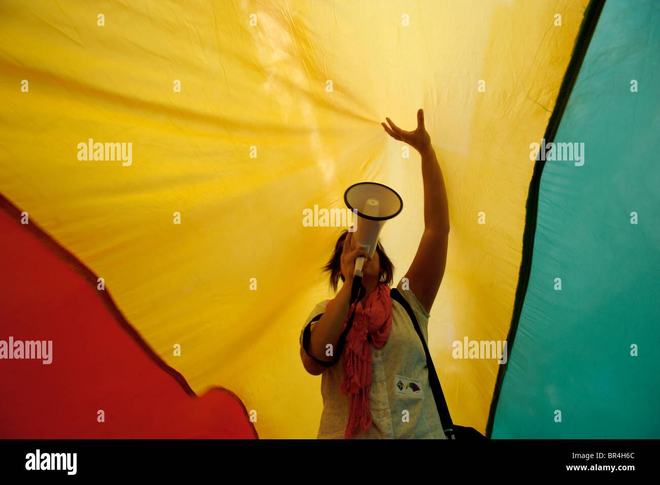 Demonstrant mit Megaphon unter rote, gelbe und grüne Flagge Stockbild