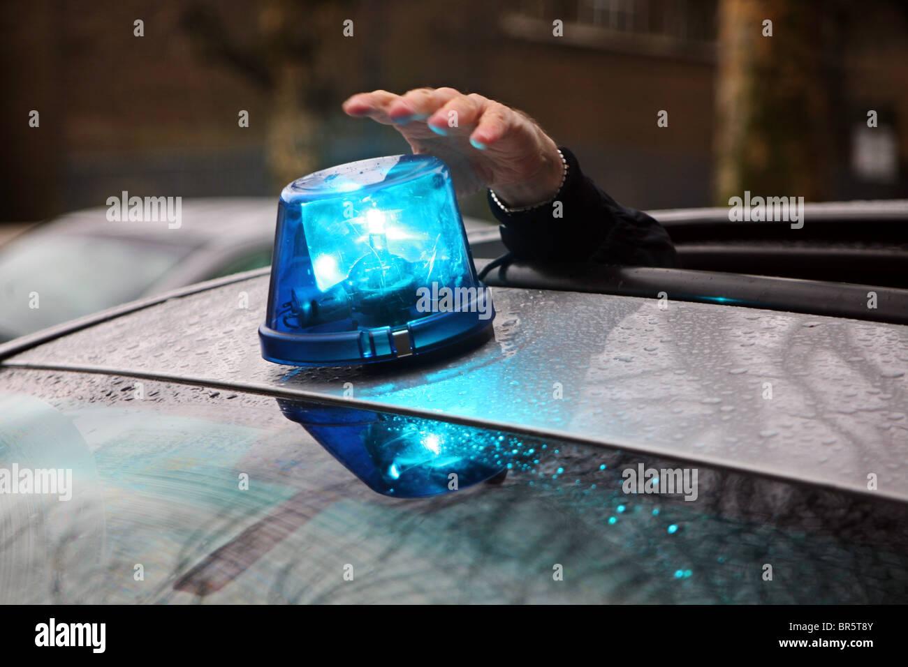 Ein Polizist stellt das Blaulicht auf Dach eine Undercover Polizei Autos. Stockbild