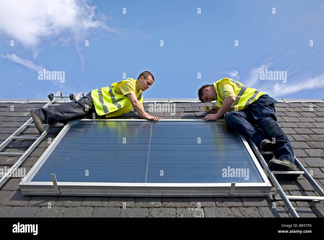 Elegant Arbeiter, Die Installation Einer Solar Thermische Panels Auf Einem Dach.  Stockbild