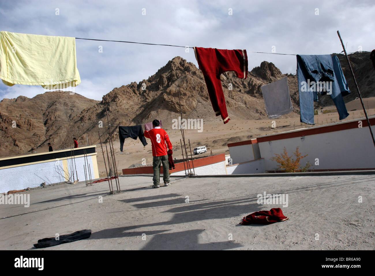 Ein Junge hängt Wäsche zum Trocknen auf dem Dach eine Knabenschule ...