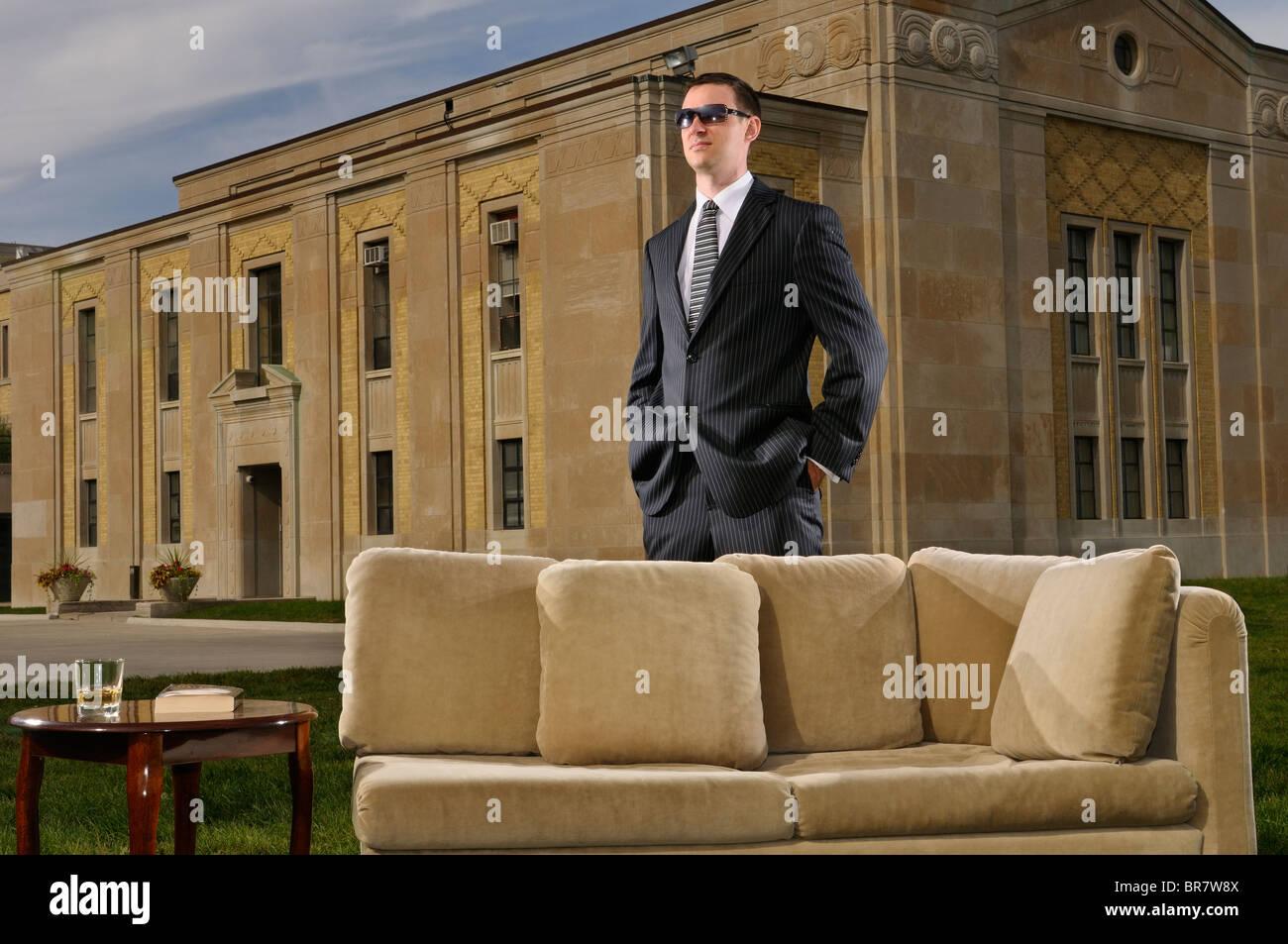 Wohlhabende junge Mann in Anzug hinter einer Couch und Tisch auf dem Rasen an einem Art Deco Mansion Stockbild
