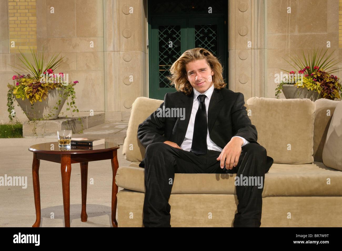 Reichen jungen Mann mit langen blonden Haaren im Anzug sitzen auf einer Couch auf der Terrasse in einem Herrenhaus Stockbild