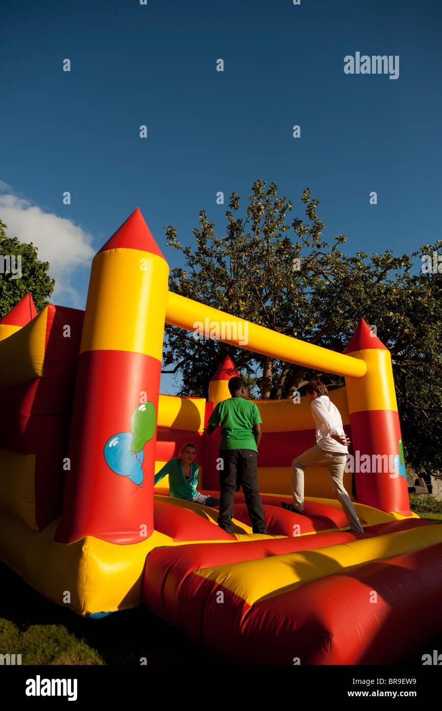 Kinder spielen auf einem aufgeblasenen Hüpfburg, UK Stockbild