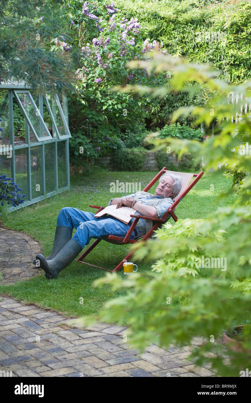 Gärtner schläft auf Liegestuhl im Garten Stockbild