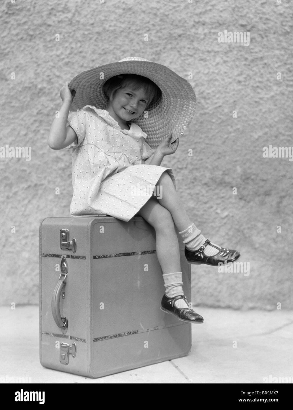 1930ER JAHRE PORTRAIT LÄCHELND MÄDCHEN SITZEN AUF KOFFER TRAGEN GROßEN STROHHUT Stockbild