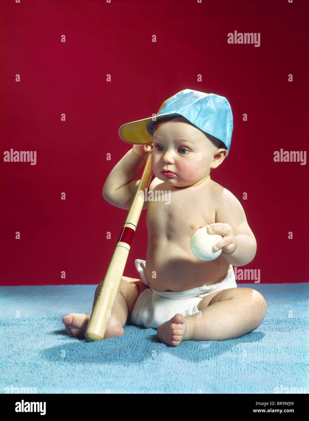 1960ER JAHRE BABY TRAGEN BLAUE BASEBALL-CAP MIT BALL UND SCHLÄGER Stockfoto