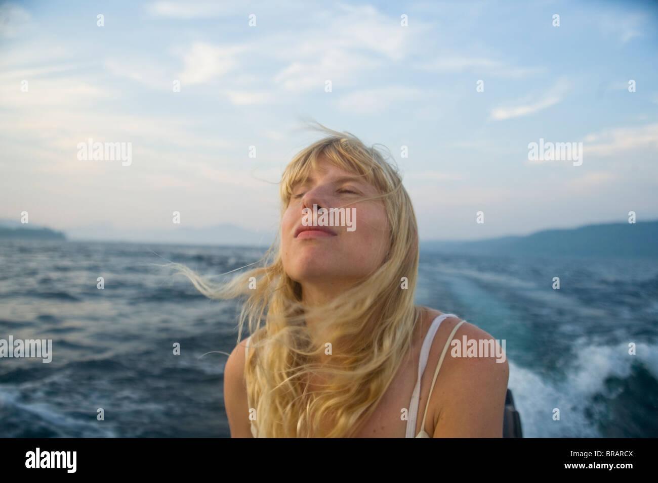 Frau genießt Wind auf Boot Stockbild