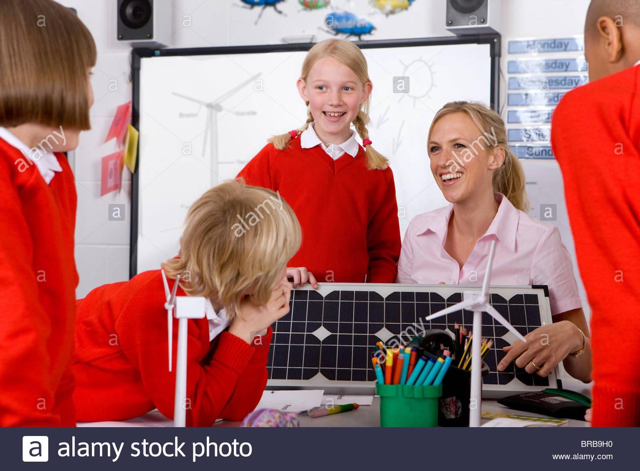 Lehrer und Schülerinnen und Schüler betrachten Solar-Panel und Modell-Windkraftanlagen Stockbild