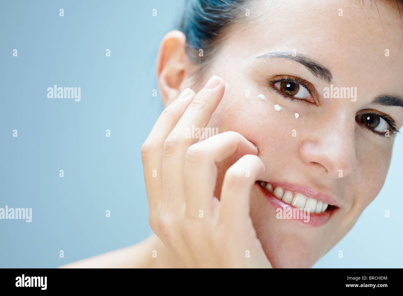 Frau Augencreme anwenden Stockbild