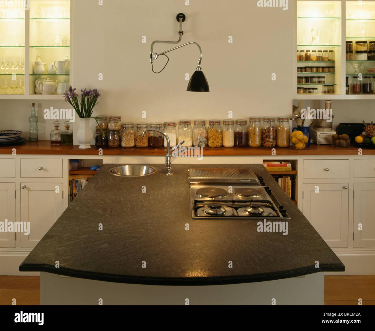 Ausschnitt Kochfeld In Insel Einheit Mit Schwarzem Corian Arbeitsplatte In  Modernen Weißen Küche Mit Wand Lampe über Vorratsdosen Auf Arbeitsplatte