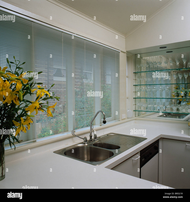 Edelstahl Doppelwaschbecken Unten Jalousie Am Fenster Uber Der Spule In Kleine Moderne Weisse Kuche Mit Glas Regale Stockfotografie Alamy