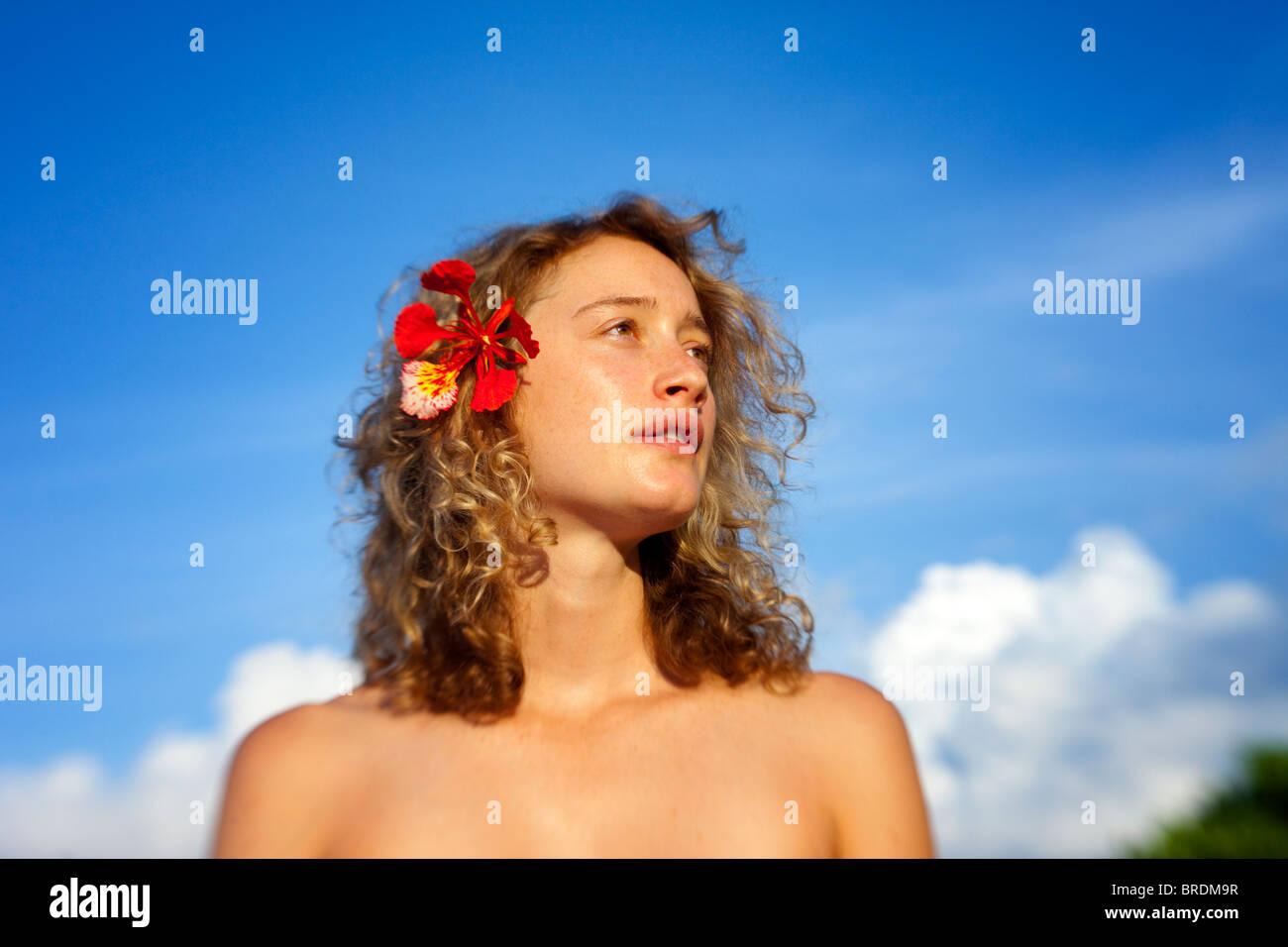 junge Frau mit Blume in lockiges Haar Stockbild