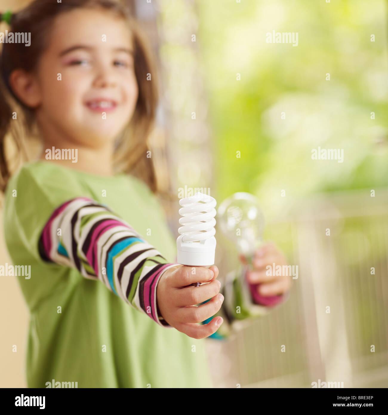 Mädchen hält die Glühbirne und lächelnd. Tiefenschärfe, Textfreiraum Stockbild