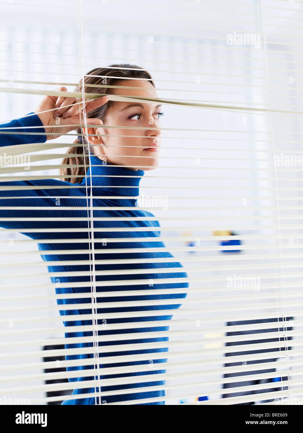 Geschäftsfrau sucht durch Jalousien Stockfoto