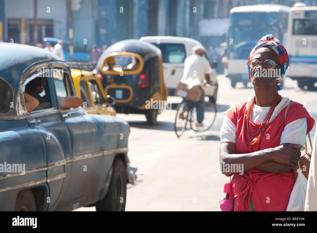 HAVANNA: CENTRO HABANA VERKEHR UND FRAU WARTEN Stockbild