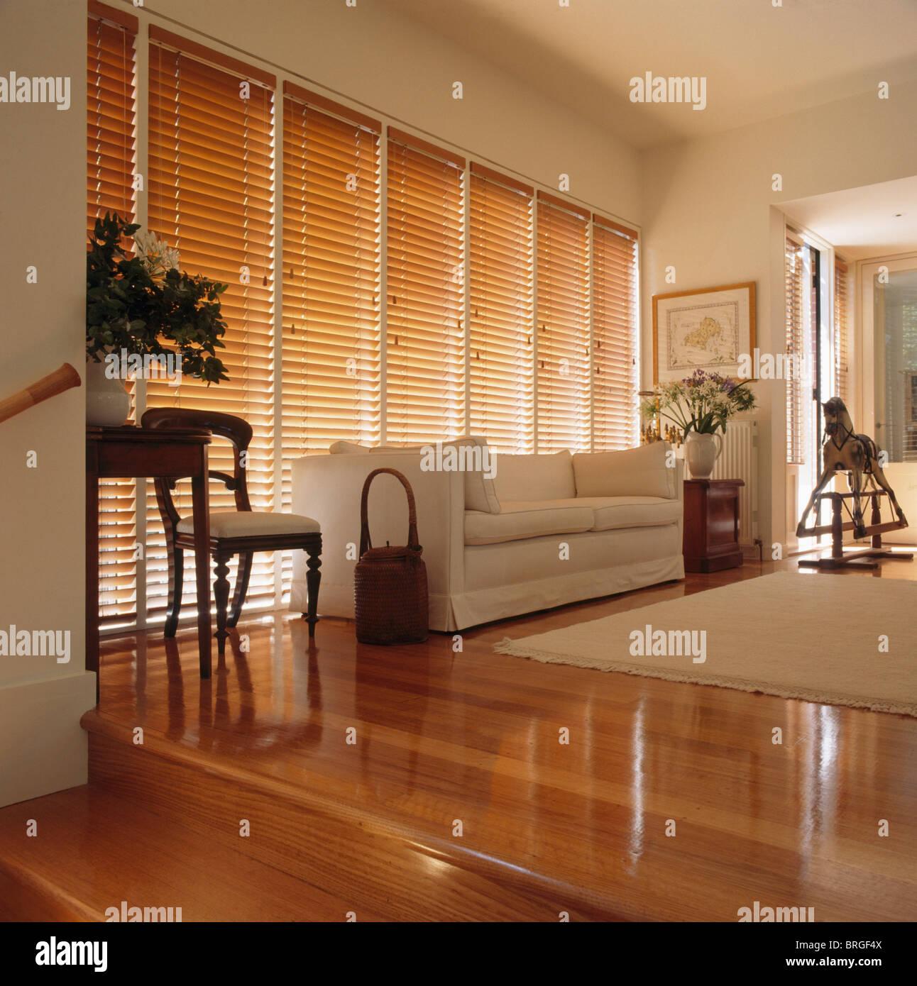 wei en sofa vor fenster mit h lzernen jalousie in modernen wei en wohnzimmer mit wei en teppich. Black Bedroom Furniture Sets. Home Design Ideas