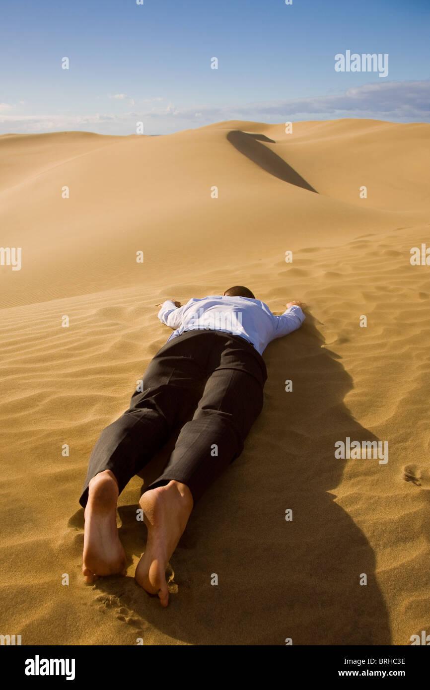Geschäftsmann tot in der Wüste Stockfoto