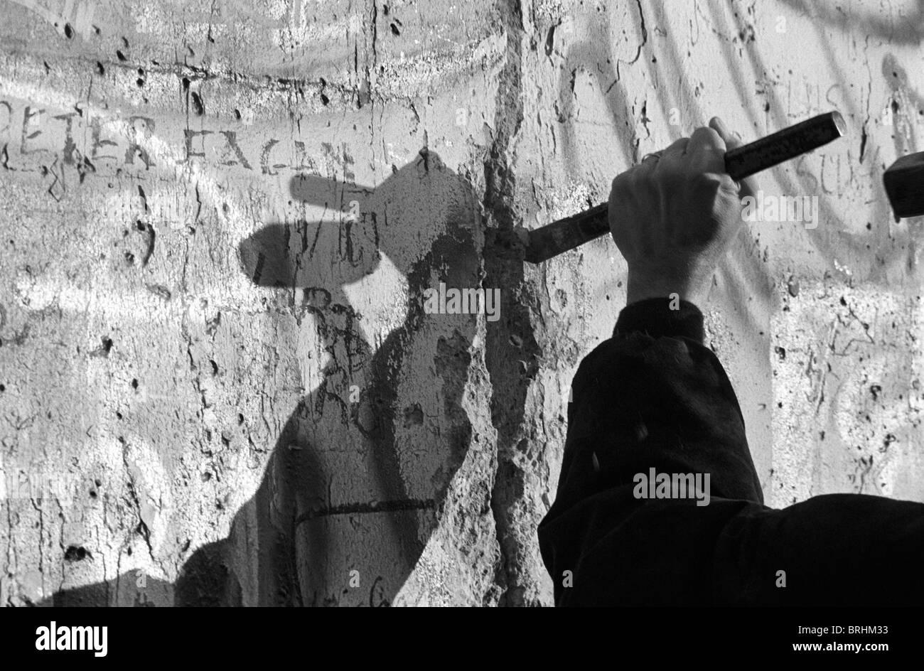 Ein West-Berliner schneidet ein Loch in der Mauer Stockbild