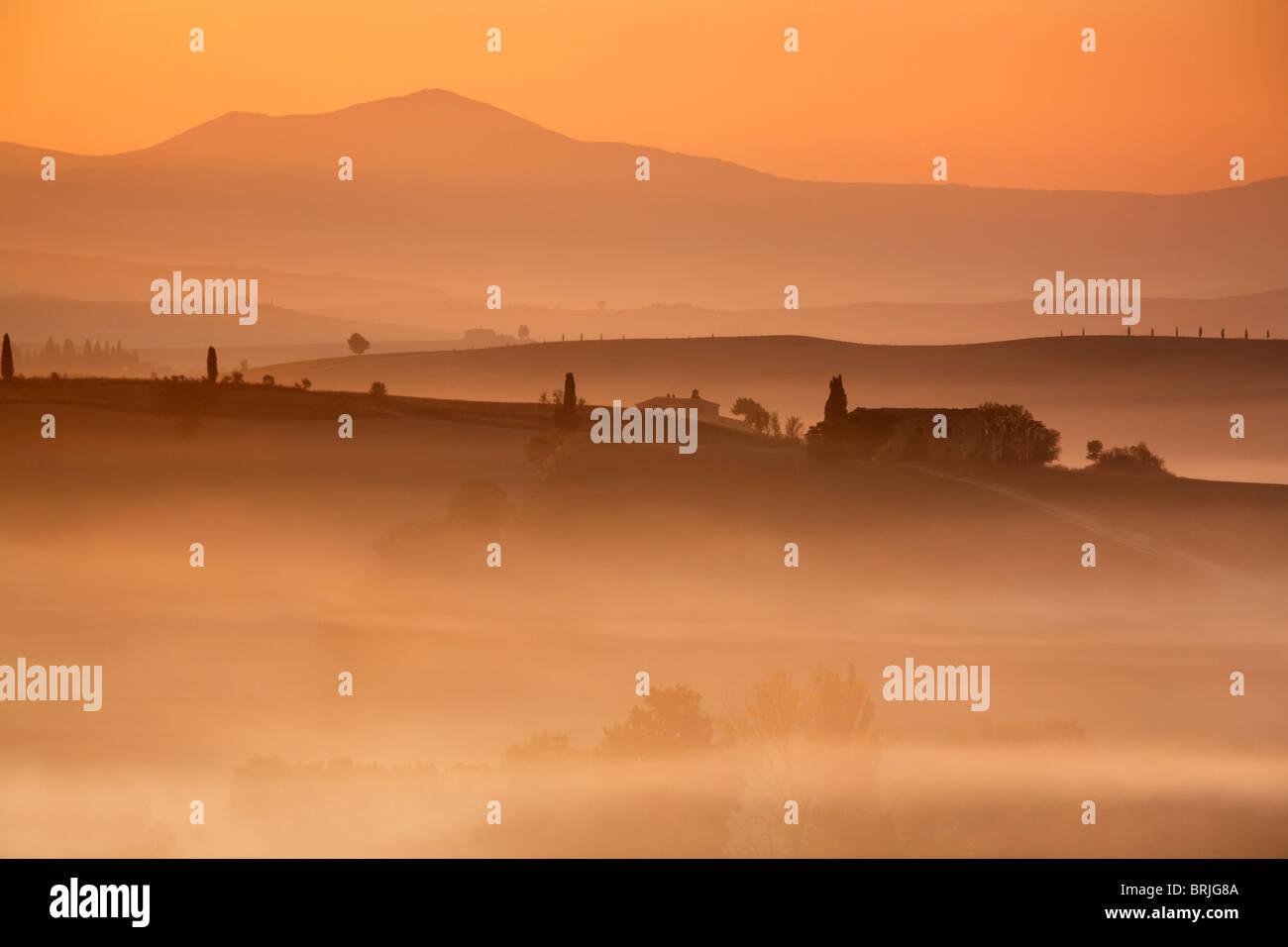 Vor Sonnenaufgang Licht malt die neblige Landschaft des Val D'Orcia in leuchtenden orange & rote Farben Stockbild