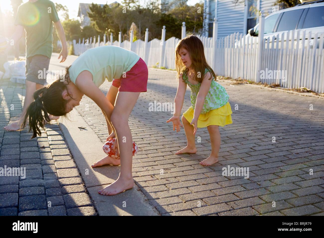 Zwei kleine Mädchen spielen Fußball in einer Gasse mit der Sonne im Hintergrund. Stockbild
