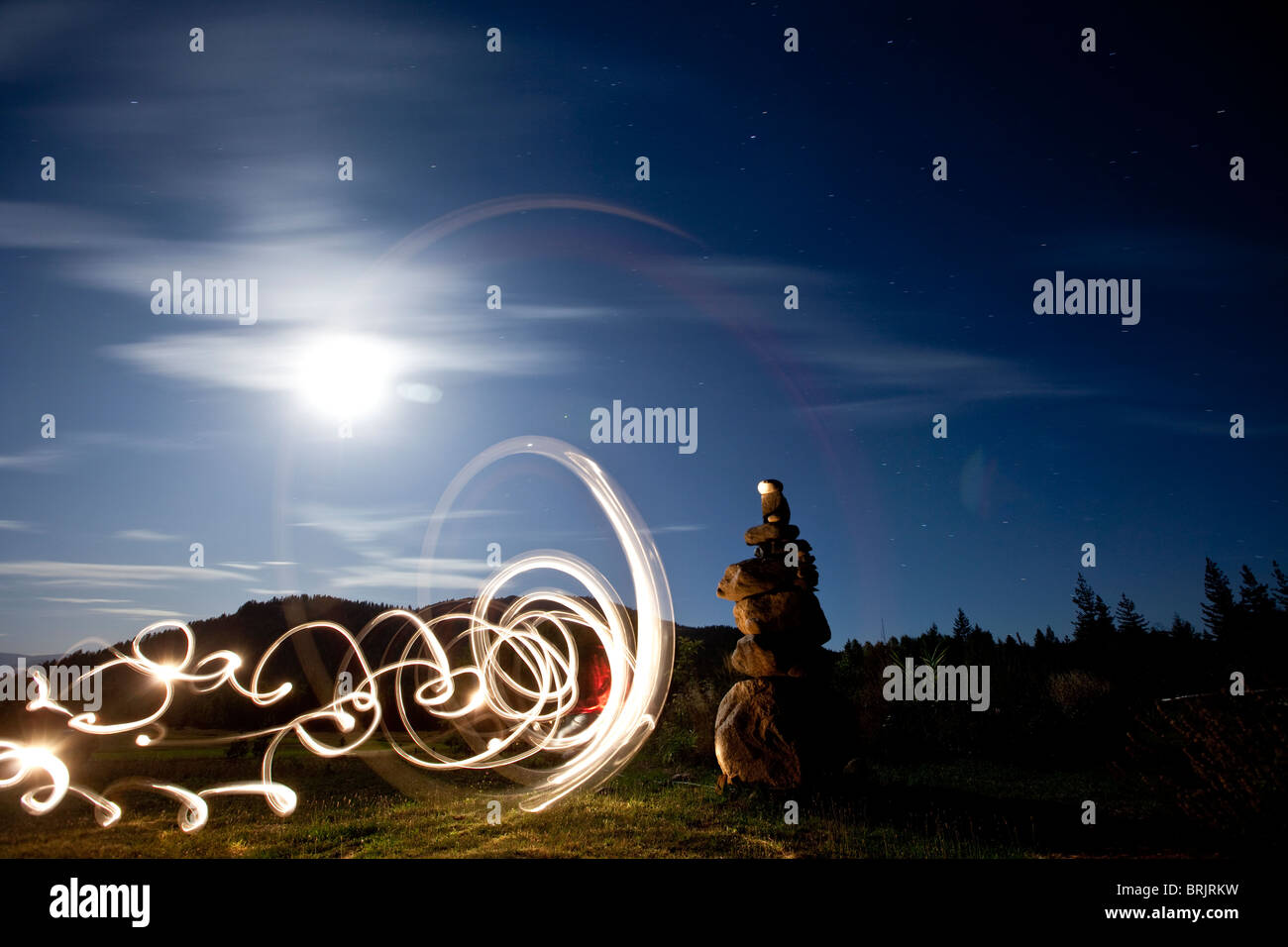Rock Cairn mit Lightpainting neben ihm und Vollmond im Hintergrund in Idaho. Stockbild