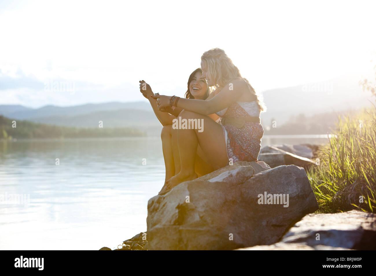 Zwei junge Frauen lachen während SMS bei Sonnenuntergang auf dem See. Stockbild