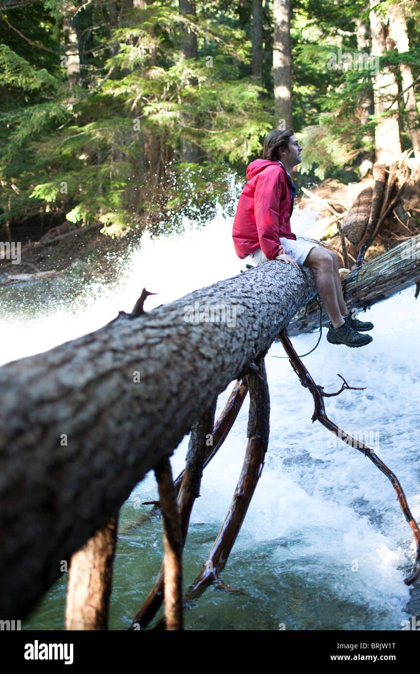Ein junger Mann sitzt auf einem Baumstamm über einem Wasserfall in Idaho. Stockfoto