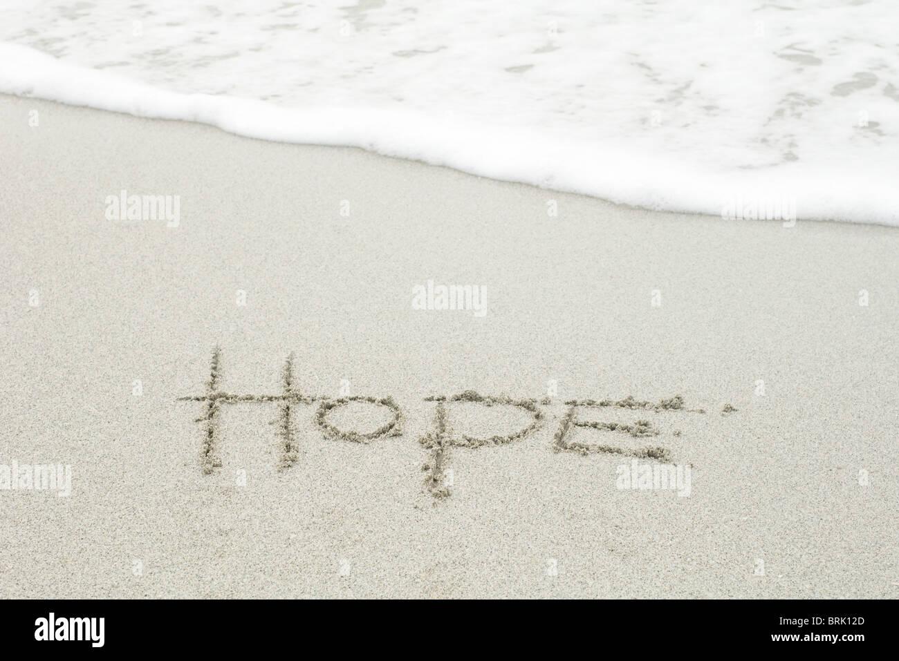 "Das Wort ""Hoffnung"" in den Sand am Strand geschrieben Stockbild"