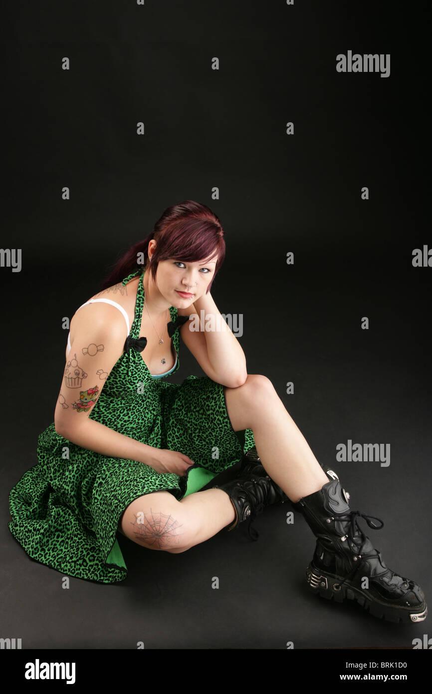 Alternative aussehendes Mädchen mit großen Stiefeln sitzen. Stockbild