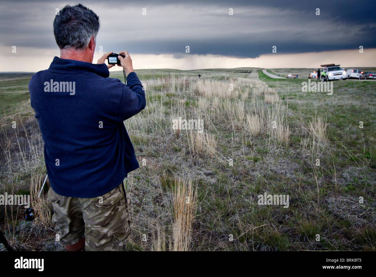 Vortex 2 Projektmitglied Herb Stein nimmt ein Foto von einer entfernten Wand-Wolke im ländlichen Wyoming, 21. Stockbild